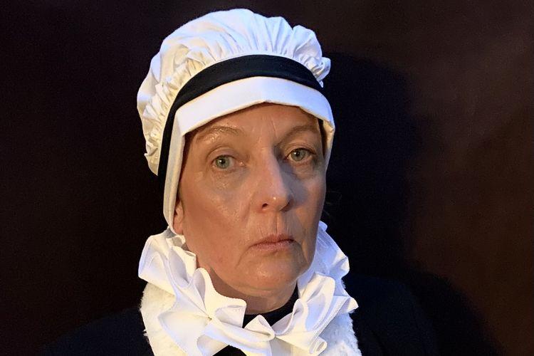 Bild der einer kostümierten Schauspielerin mit einer weißen Haube und einem weißen Kragen.