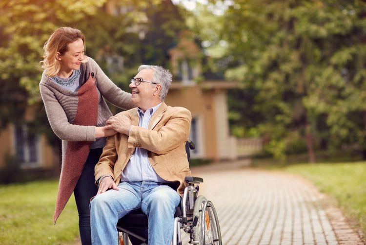 Bild eines älteren Mannes im Rollstuhl, der lächelnd die Hand einer Frau hält