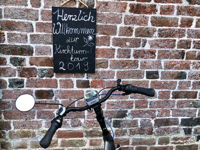 Bild Krummhörner Kirchturmtour Wand mit Schild