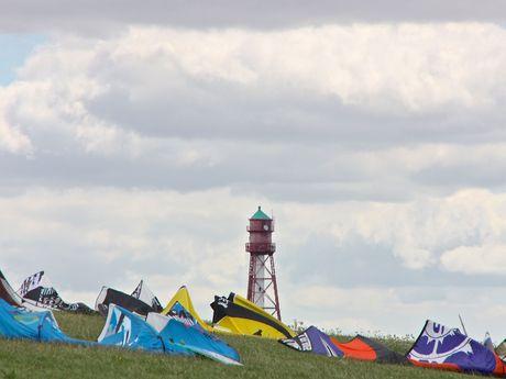 Kitesegel auf dem Deich in Upleward mit dem Blick auf den Campener Leuchtturm