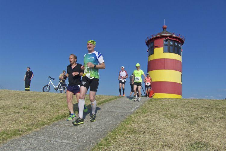 Läufer bei der Veranstaltung EWE Nordseelauf vor dem Pilsumer Leuchtturm