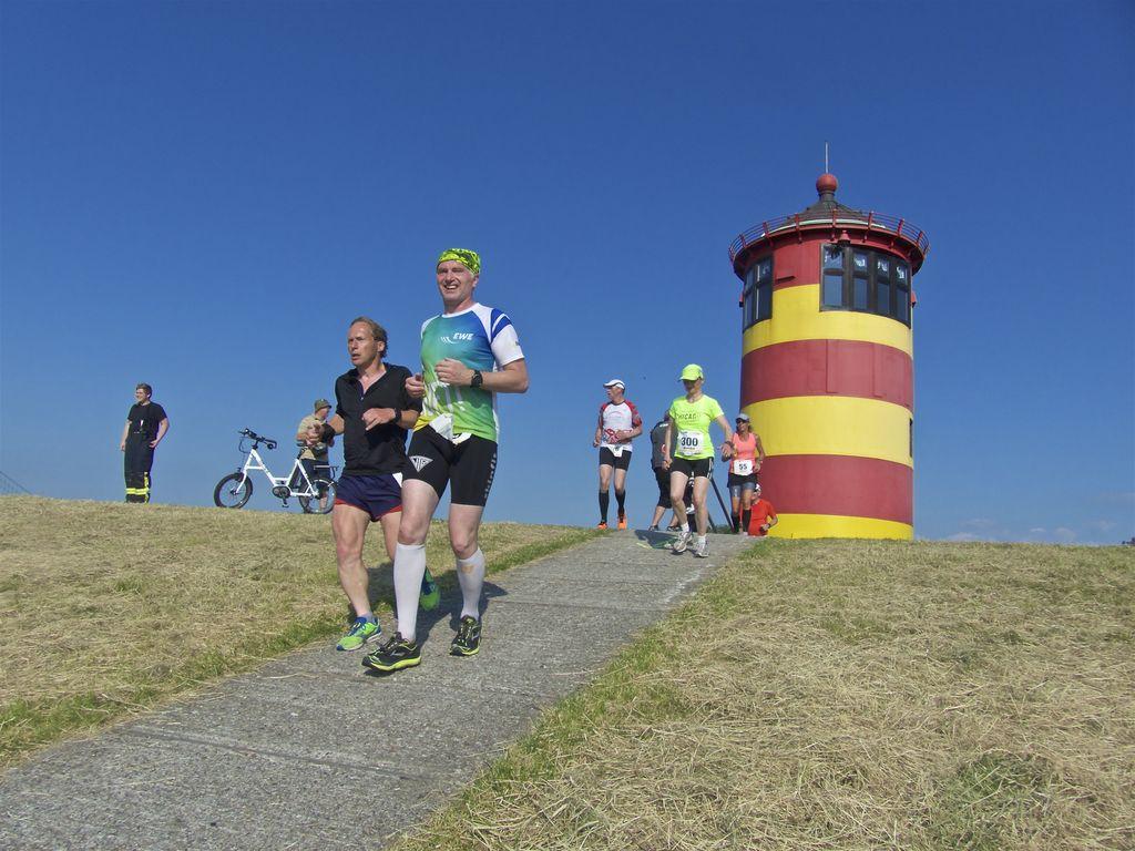 Läufer vor dem Pilsumer Leuchtturm beim EWE Nordseelauf in Greetsiel
