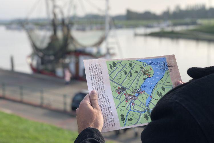 Karte in einer Hand vor dem Hafen Greetsiel